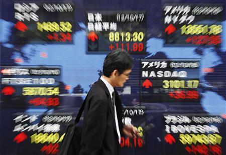 A man uses a mobile phone in front of an electronic board displaying market indices from around the world, outside a brokerage in Tokyo